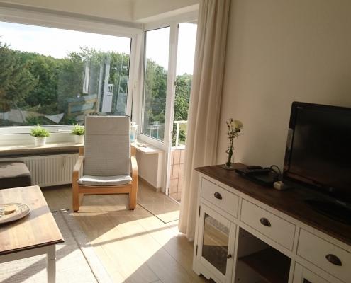 Ferienwohnung Grömitz - Wohnbereich mit Sessel und Anrichte
